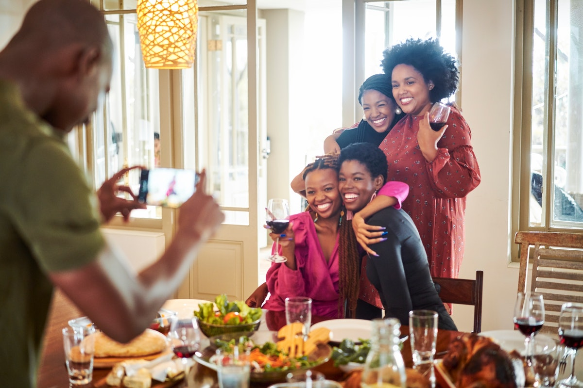 A group of happy women pose for a picture at their Friendsgiving dinner table.
