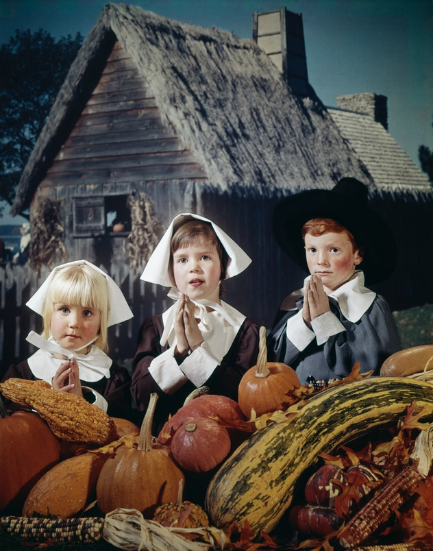Children posing as pilgrims with pumpkins.