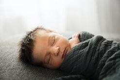 newborn baby in gray blanket