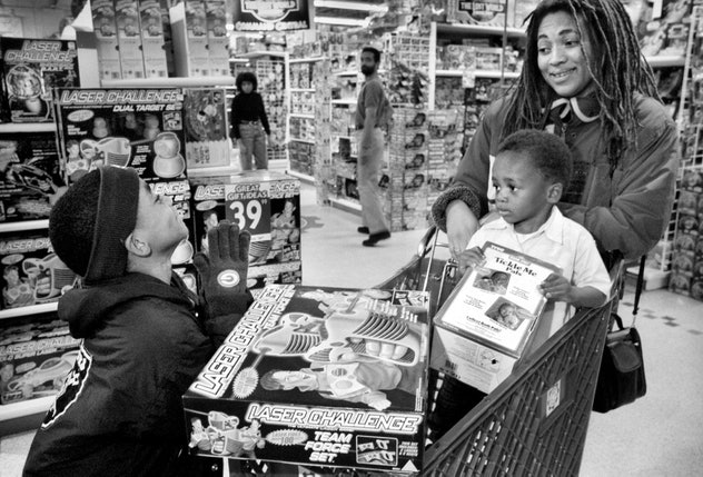 A mother shops with children at a toy store for a Tickle Me Elmo.