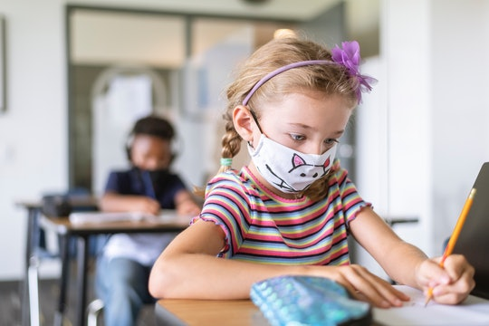 little girl in mask at school