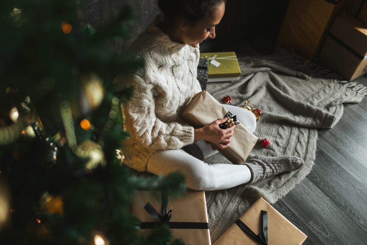 A woman wraps presents for Christmas, while sitting next to her tree.