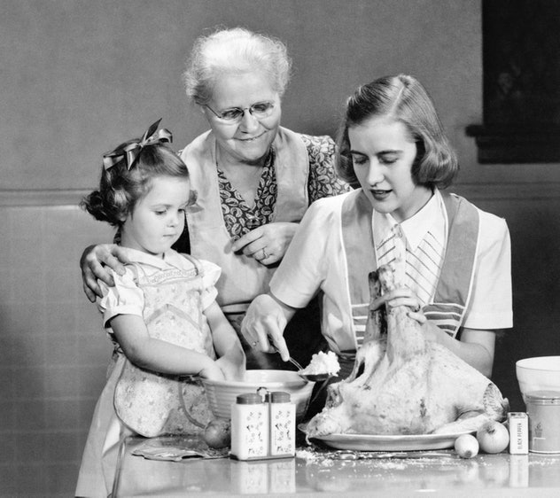 A mother, grandmother, and daughter all stuff a turkey.