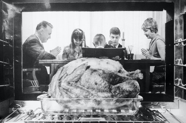 A turkey in an oven with family in the background.