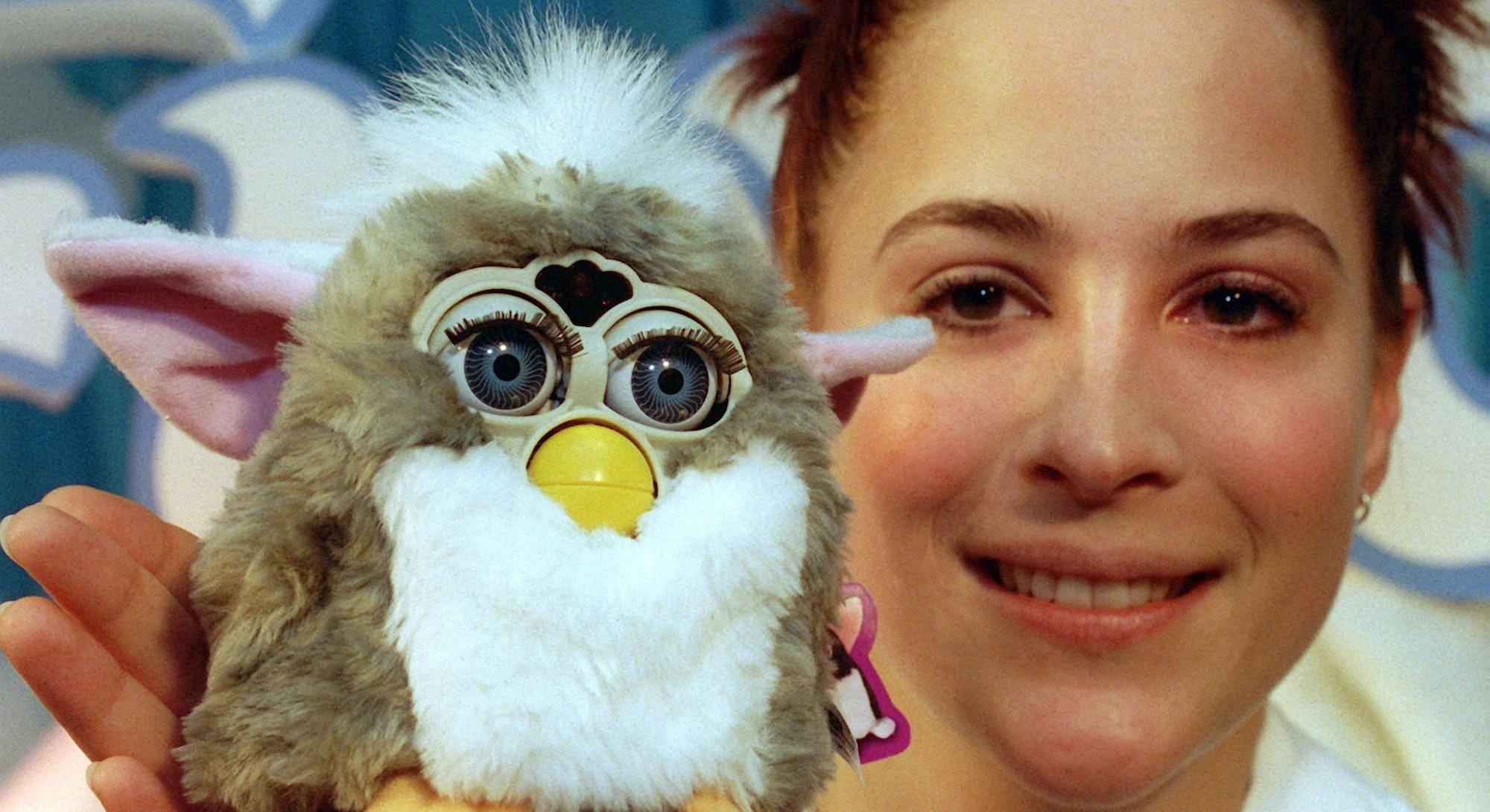 A woman holding a Furby