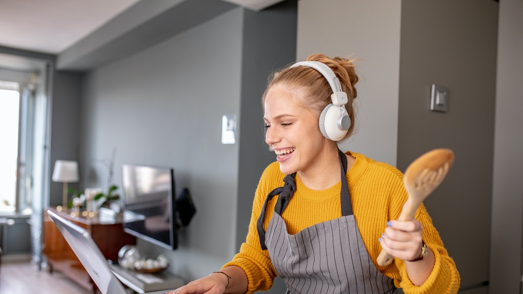 A happy woman holding a wooden spoon checks her laptop while cooking in the kitchen.