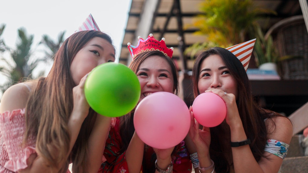 Three friends, wearing party hats, blow up balloons at a birthday party.
