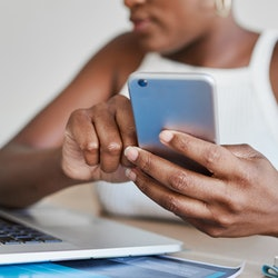 A woman tweets on her phone while looking at her computer. Twitter announced Fleets, disappearing Tweets, are here to stay.