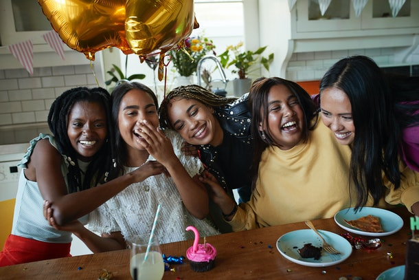 A group of friends hug at a birthday party.