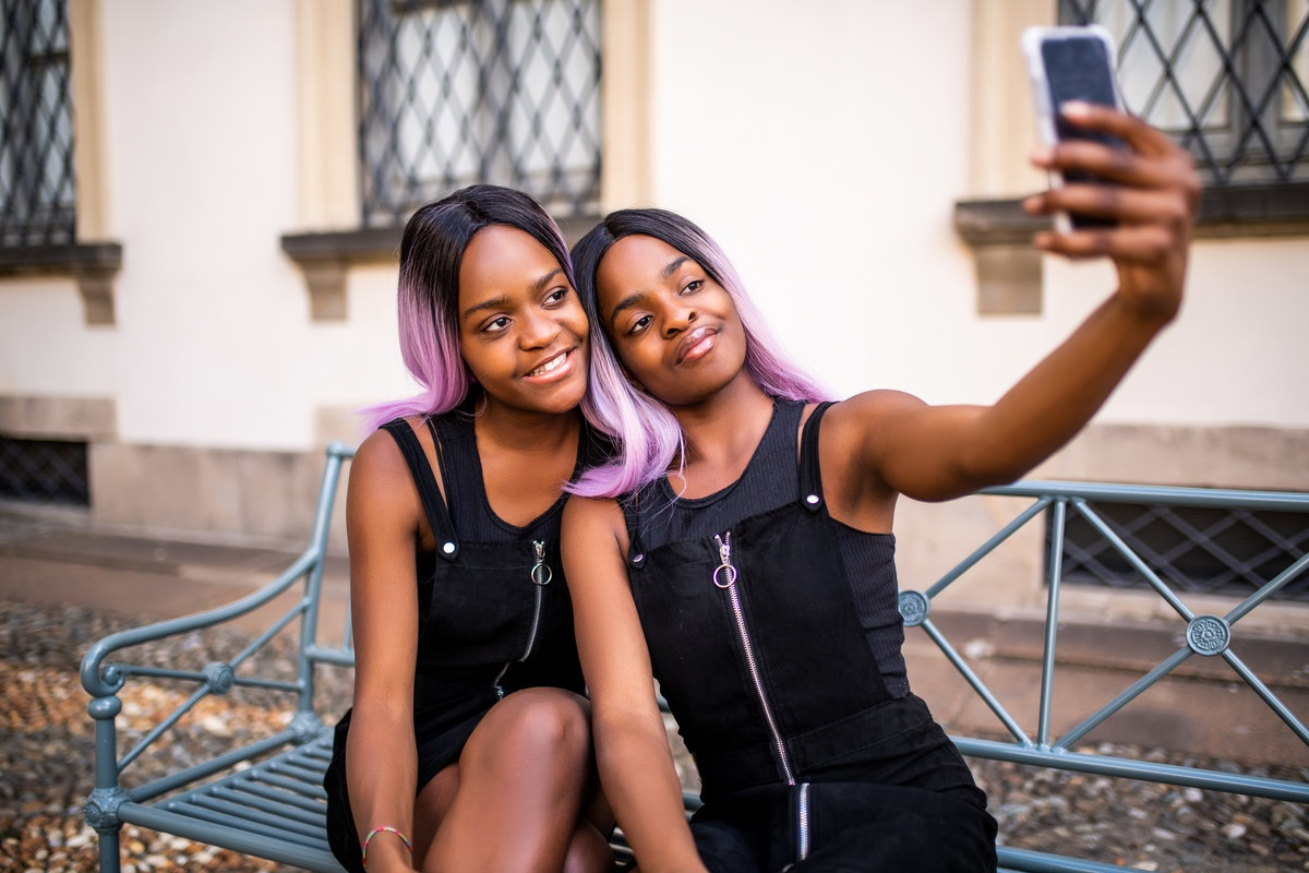 Two twins with black and pink hair pose for a selfie on a bench outside.