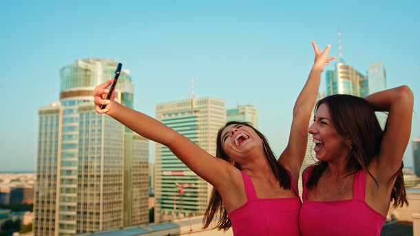 Two sisters in pink dresses pose for a silly selfie on a rooftop.