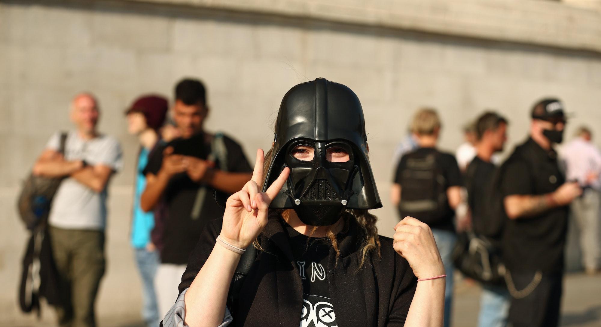 A demonstater in a Darth Vader mask star wars political protest