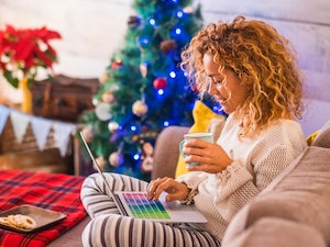 A woman wearing loungewear with a plate of cookies and mug in hand, sits by the Christmas tree, looking at holiday shopping on her laptop at home.