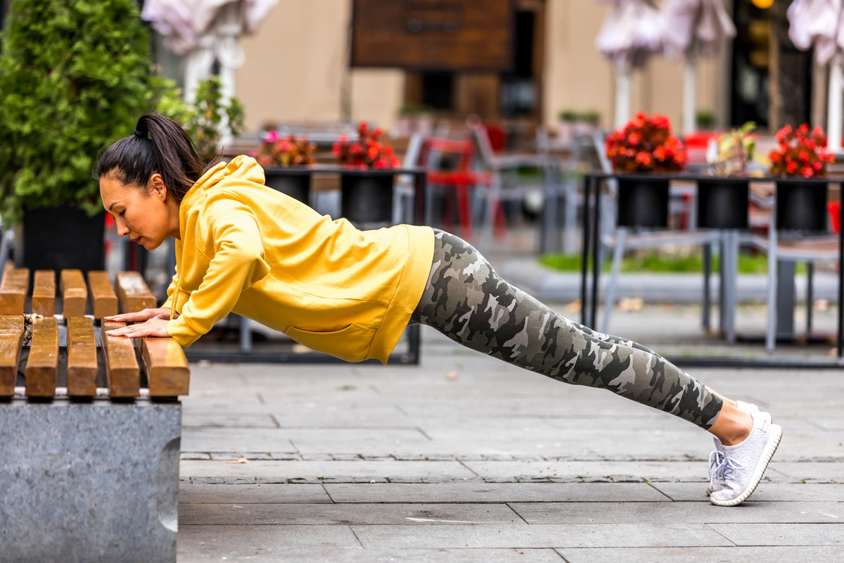 A person wearing leggings and a yellow jacket performs an elevated pushup on a bench. Elevated pushups can challenge your core more than pushups on your knees.