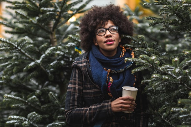 A young Black woman stands amongst a row of evergreen trees and holds a coffee cup.
