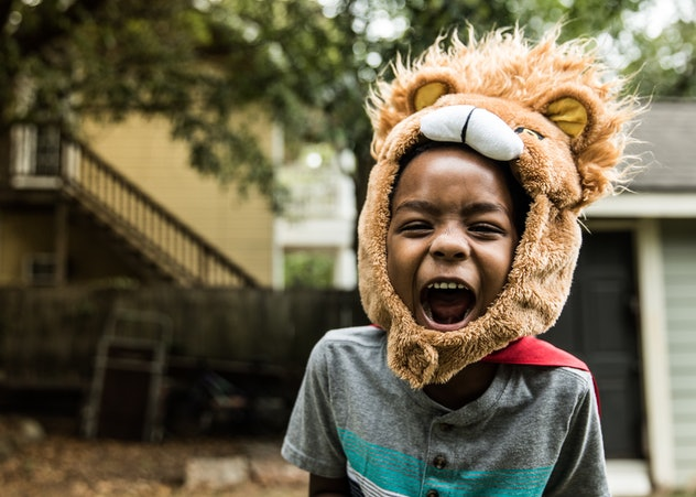 This child is playing with a lion costume.