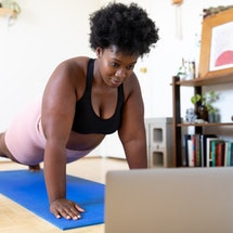 A person with natural hair holds a plank position while looking at their laptop in their living room. Pushup routines can get old quickly, but there are plenty of pushup variations you can use.
