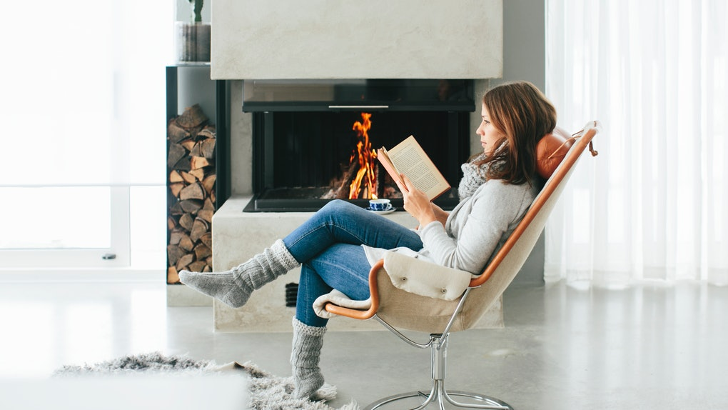A young woman reads a book while sitting in a chair next to a fire in a winter outfit.