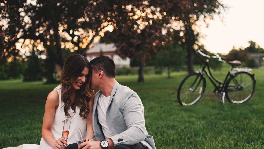 A happy couple enjoys a glass of wine on a bicycle picnic out in the park at sunset.