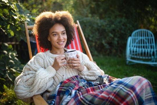 Woman wearing sweater and blanket outside.