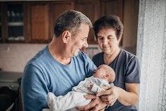 Grandparents holding newborn baby.