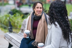 pregnant woman and friend drinking coffee on bench