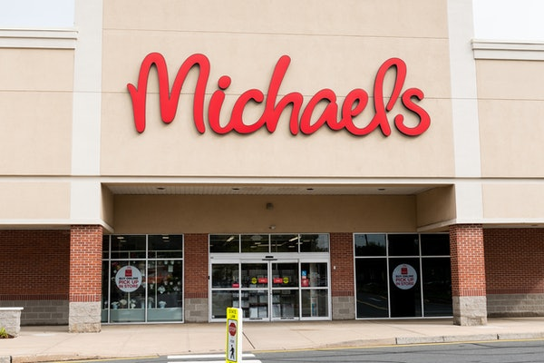 """A Michaels store front has """"buy online"""" signs on the windows on a sunny day."""
