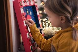 little girl opening door on advent calendar