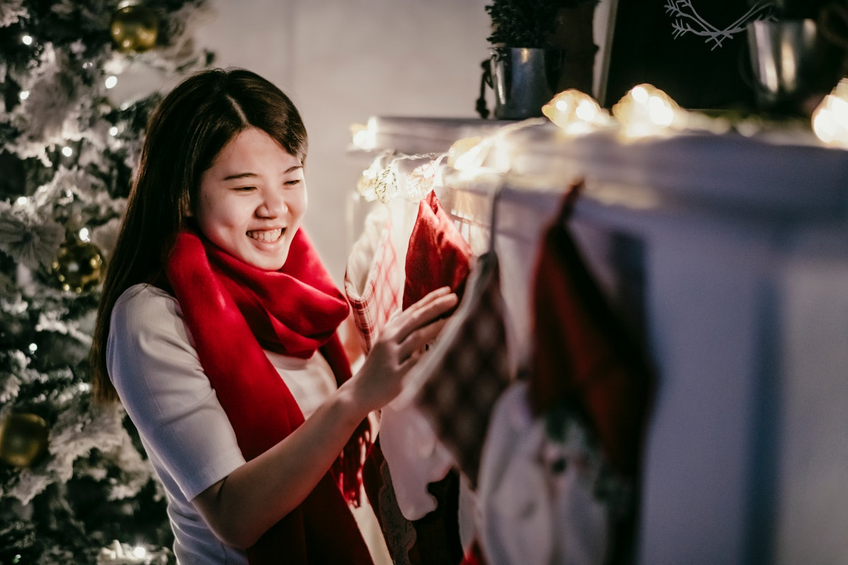 A woman admires some holiday stockings hung on the chimney at Christmas.