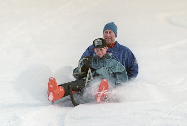 Prince Charles goes sledding with Prince Harry in 1997.