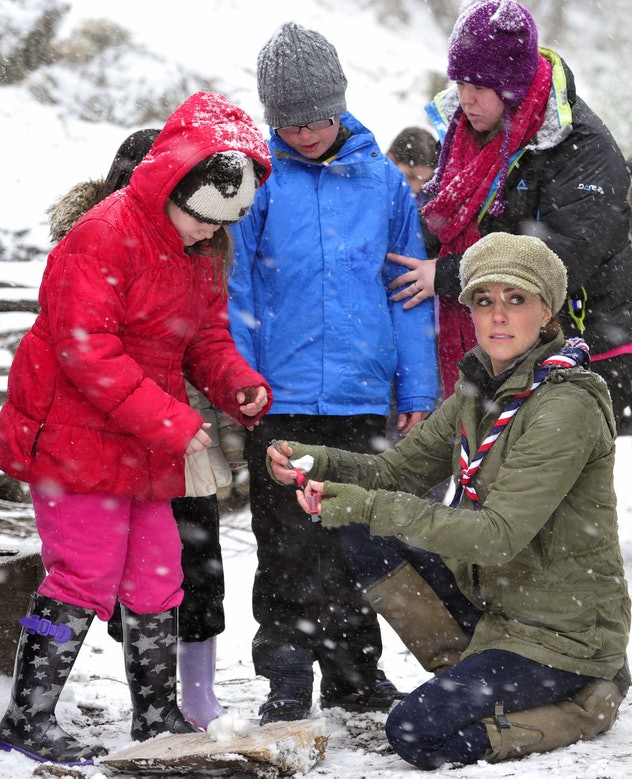Kate Middleton helps young Scouts light a fire in the snow in 2013.
