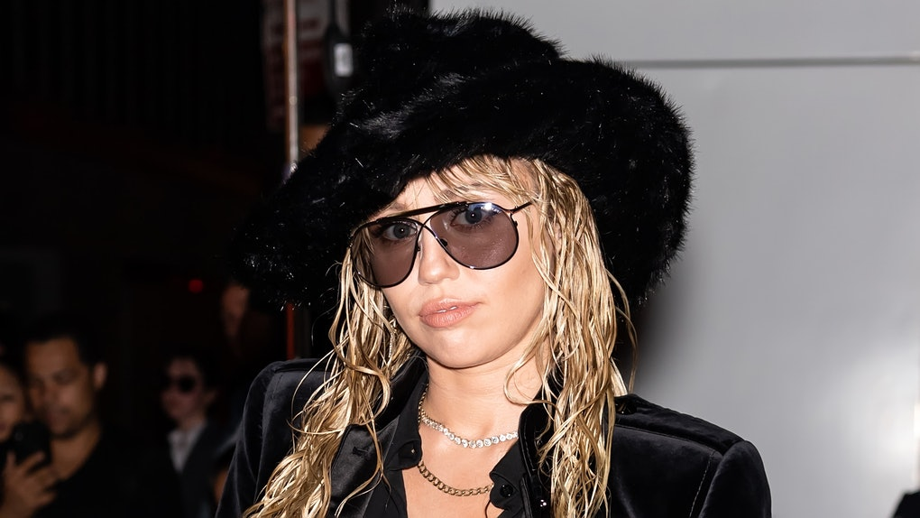 Miley Cyrus wears a black furry hat and sunglasses on the red carpet with a wet hair style.