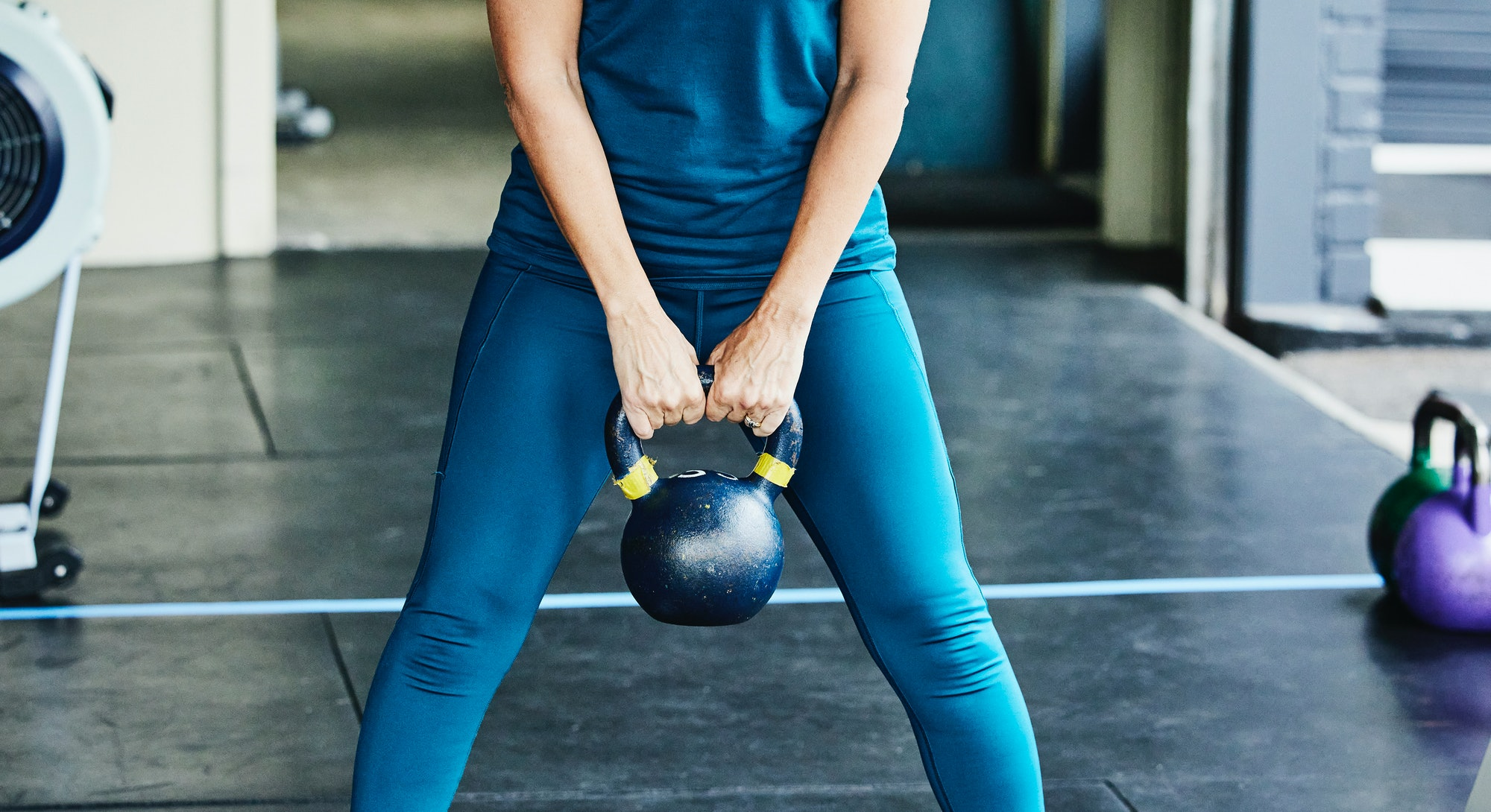A person wearing a mask performs a kettlebell deadlift in the gym. You don't need a lot of space to have a powerful kettlebell workout.