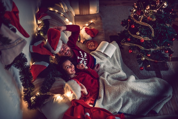 A couple snuggles in their festively-decorated home for the holidays to watch Christmas movies.