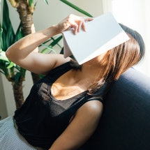 A woman naps on a couch with a book over her face during Thanksgiving week. Exercise guilt is real; ...