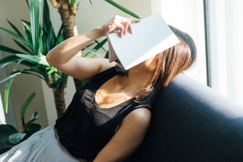 A woman naps on a couch with a book over her face during Thanksgiving week. Exercise guilt is real; experts explain how to overcome it.