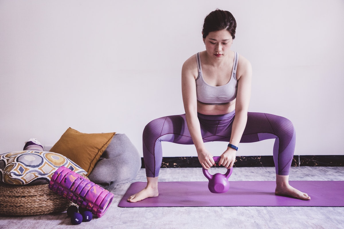 A person performs a sumo kettlebell squat in her living room. Kettlebells are perhaps the most versatile exercise equipment.