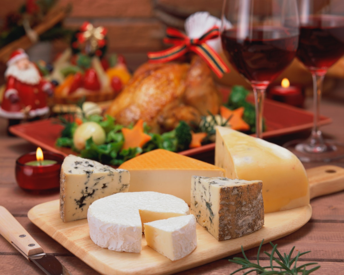 A holiday cheese board is placed on a table next to red wine and a turkey.