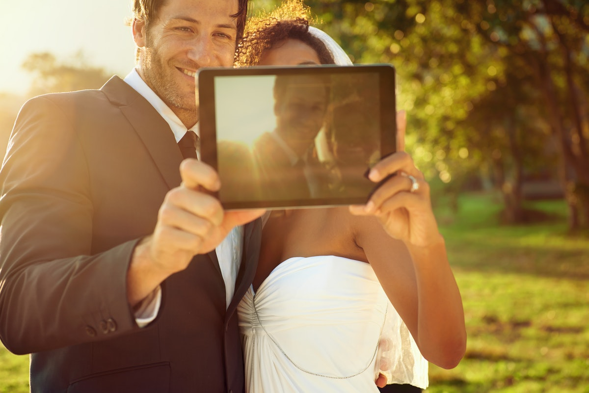 A happy couple snaps a selfie with their tablet outside at sunset.