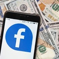 Facebook icon on a phone over a pile of money, representing a class action settlement payout.