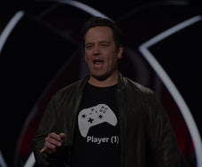 The head of Xbox, Phil Spencer, can be seen mid-speech at an Xbox conference. Spencer is wearing a shirt with a controller on it. He has a jacket on.