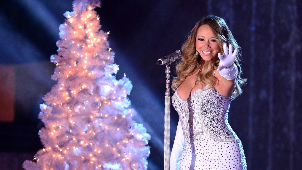 Mariah Carey wearing a sparkly white gown and gloves, performs next to a white Christmas tree.