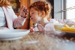 little girl being fed soup