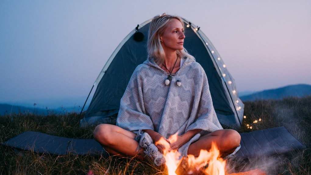 A young woman with blonde hair sits next to a campfire and tent on a grassy mountain.