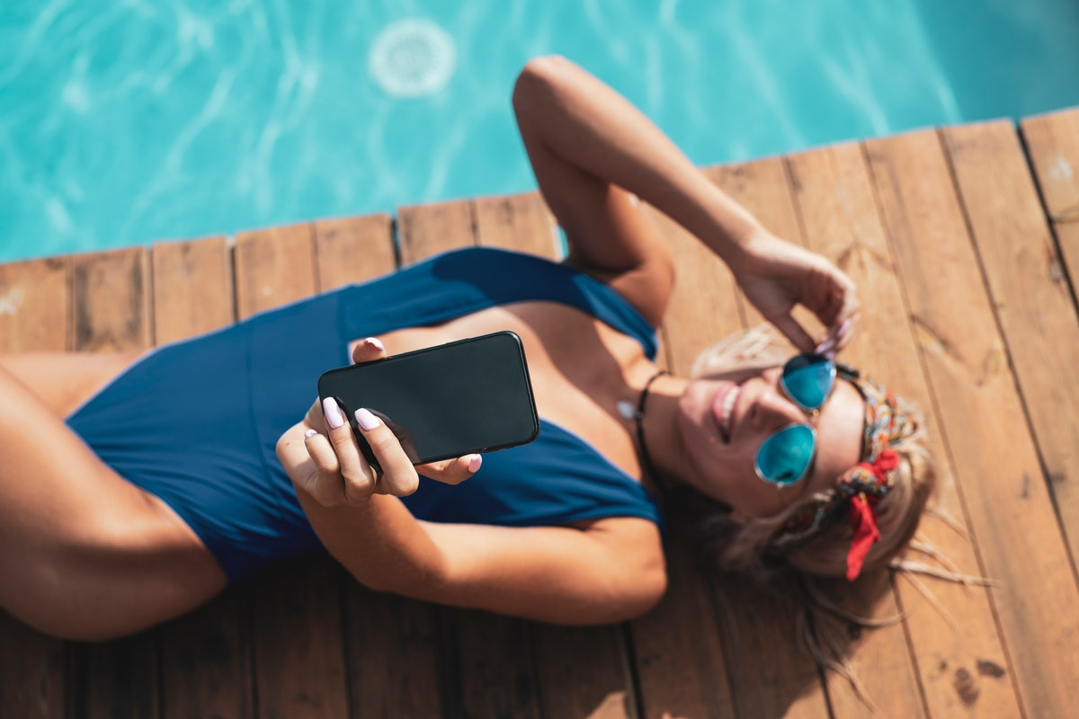 A blonde woman in blue sunglasses, a blue bathing suit, and red hair scarf lays down next to a pool and takes a selfie.