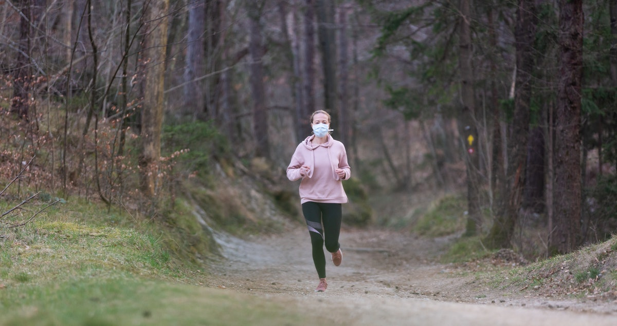 A person wears a hoodie and a mask while running through on a trail. Turning off your music can boost your internal motivation for a run.