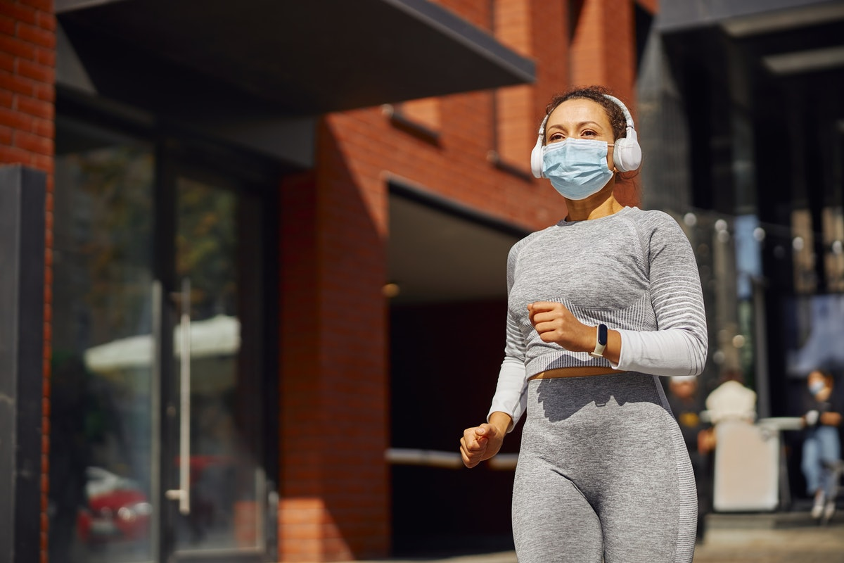 A person wears a mask, headphones, and a grey running outfit while jogging in the city. Spice up your running routine by treating yourself to new running gear.