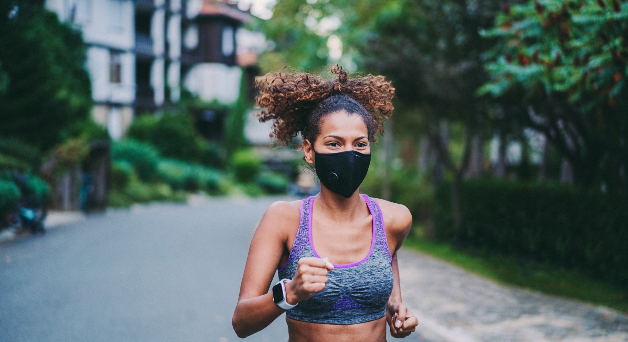 A person with natural hair and a sports bra wears a black mask while running outside. Your run doesn't have to get boring, even if you jog every day.