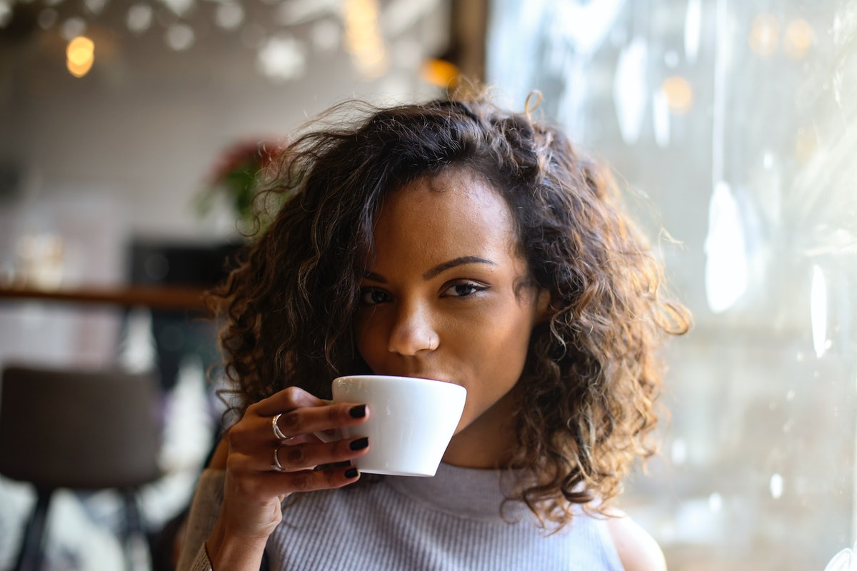 A young Black woman with short, curly hair sips on a cup of espresso while sitting in a cafe.