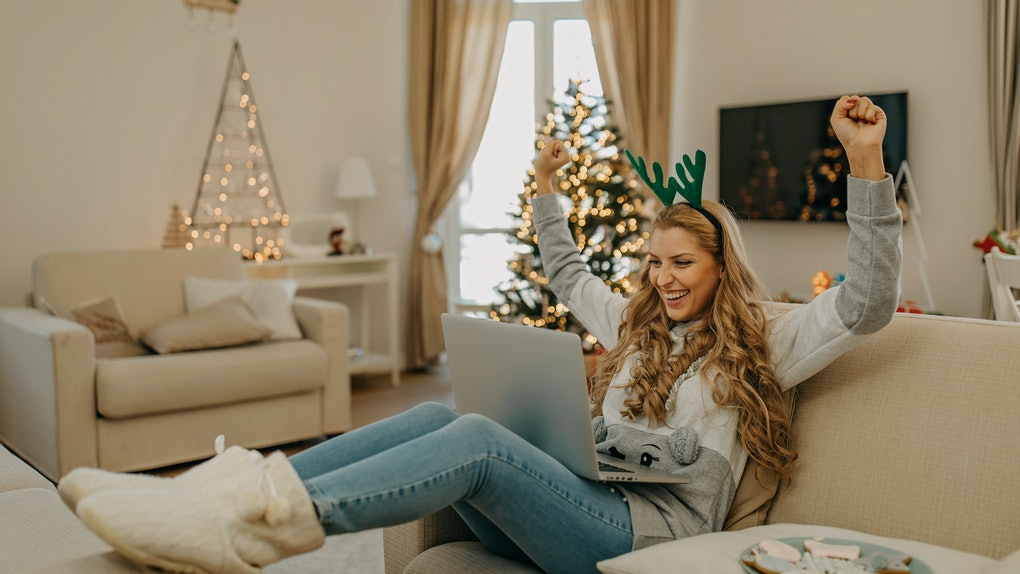 A happy woman who's dressed up for Christmas looks at her laptop on the couch.